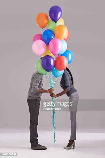 Stealing a kiss behind the balloons
