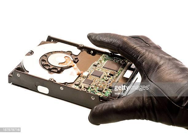 Stehlen Daten hand in schwarzen Handschuhen, harddrive