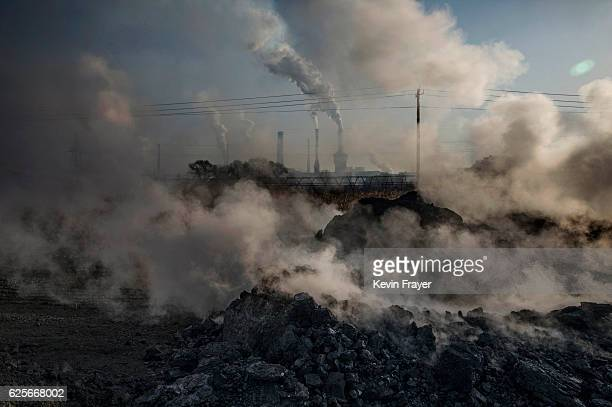 Steam and smoke from waste coal and stone rises after being dumped next to an unauthorized steel factory on November 3 2016 in Inner Mongolia China...