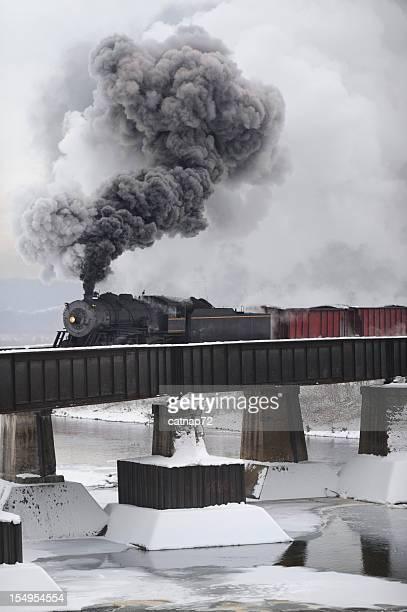 Steam Locomotive Train Crossing Railroad Bridge in Winter Snow