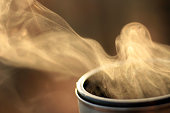 Steam of hot tea in a close-up against the sunlight; Copy space; Shallow depth of field