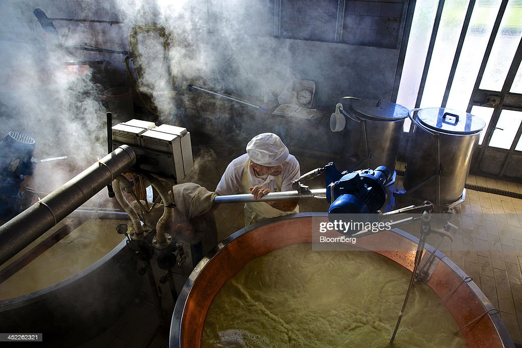Steam rises from a vat of milk as a master cheese maker checks the liquid's density during the Parmigiano Reggiano cheese manufacturing process at Il Trionfo cheese makers in San Secondo Parmense, Italy, on Tuesday, Nov. 26, 2013. Italian borrowing costs dropped at an auction of six-month bills as investors await signals from the European Central Bank about further stimulus. Photographer: Gianluca Colla/Bloomberg via Getty Images