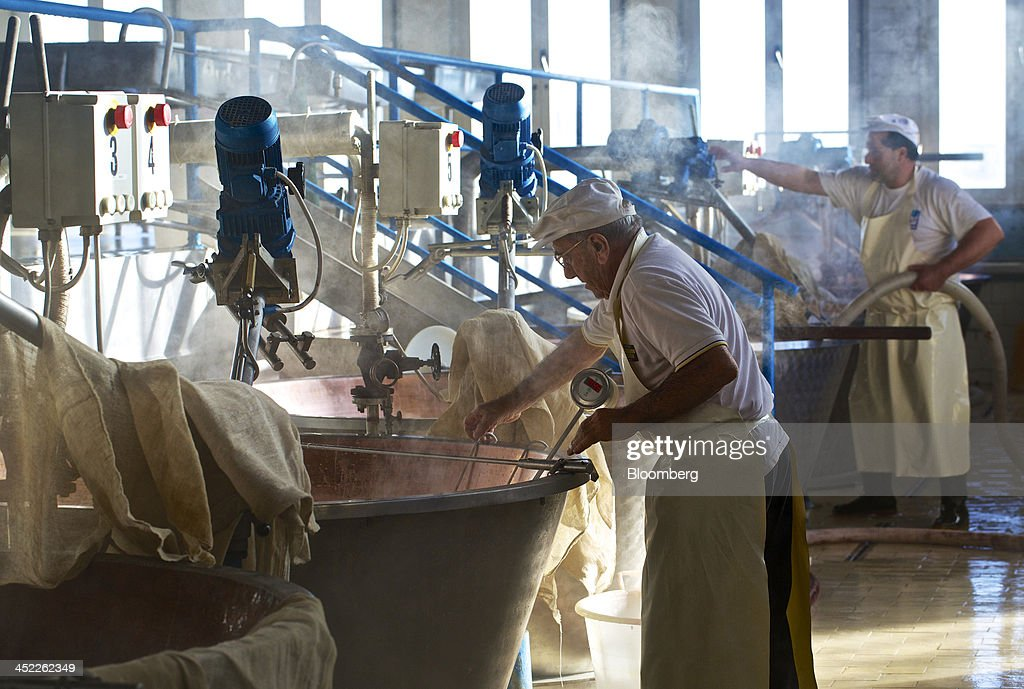 Steam rises from a vat of milk as a master cheese maker checks the liquid's density and temperature during the Parmigiano Reggiano cheese manufacturing process at Il Trionfo cheese makers in San Secondo Parmense, Italy, on Tuesday, Nov. 26, 2013. Italian borrowing costs dropped at an auction of six-month bills as investors await signals from the European Central Bank about further stimulus. Photographer: Gianluca Colla/Bloomberg via Getty Images