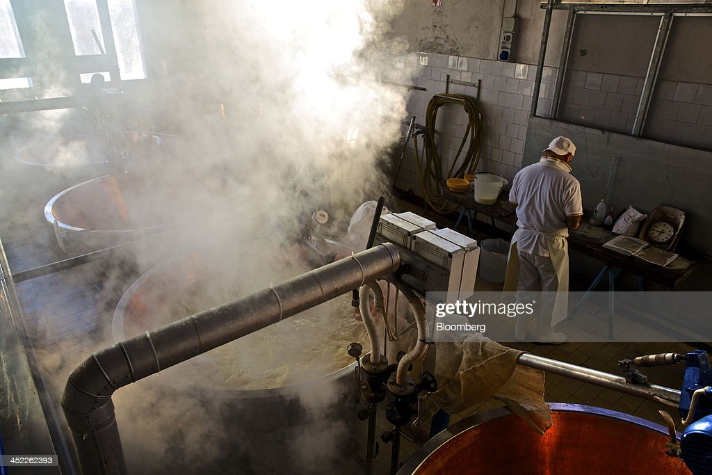 Steam rises from a vat of milk as a master cheese maker works at a bench during the Parmigiano Reggiano cheese manufacturing process at Il Trionfo cheese makers in San Secondo Parmense, Italy, on Tuesday, Nov. 26, 2013. Italian borrowing costs dropped at an auction of six-month bills as investors await signals from the European Central Bank about further stimulus. Photographer: Gianluca Colla/Bloomberg via Getty Images