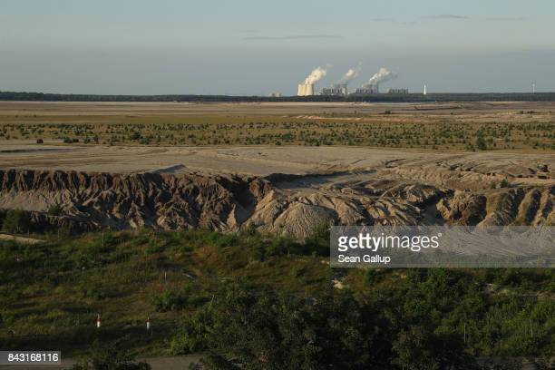 Steam rises from cooling towers at the Jaenschwalde coalfired power plant behind land recovered from the former Cottbus Nord openpit coal mine on...