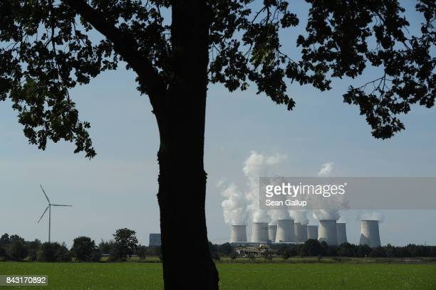 Steam rises from cooling towers at the Jaenschwalde coalfired power plant near a lone wind turbine on September 5 2017 near Peitz Germany Germany is...