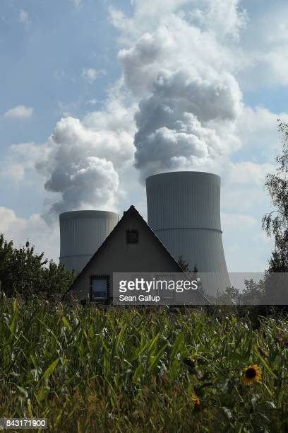 Steam rises from cooling towers at the Schwarze Pumpe liginite coalfired power plant near a house and a cornfield on September 5 2017 in Spremberg...