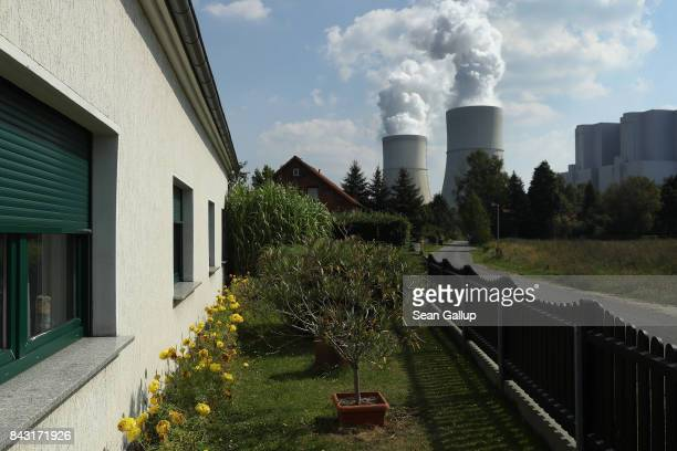 Steam rises from cooling towers at the Schwarze Pumpe liginite coalfired power plant near a residential district on September 5 2017 in Spremberg...