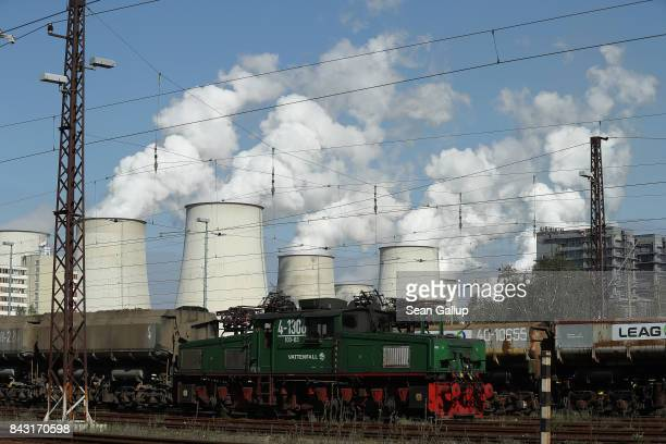 Steam rises from cooling towers next to a rail yard at the Jaenschwalde coalfired power plant on September 5 2017 near Peitz Germany Germany is...