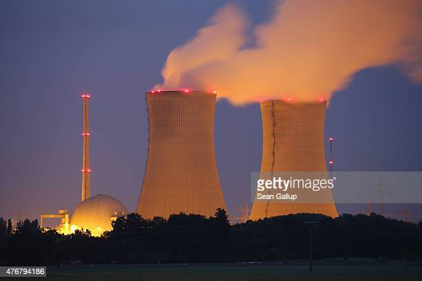 Steam rises from the cooling towers of the Grafenrheinfeld nuclear power plant at night on June 11 2015 near Grafenrheinfeld Germany The...