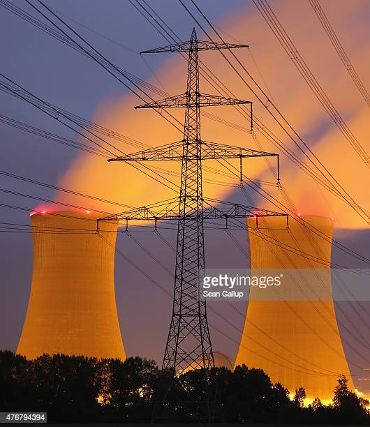 Steam rises from the cooling towers of the Grafenrheinfeld nuclear power plant as an electricity pylon stands before it at night on June 11 2015 near...