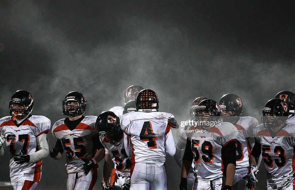 Steam rises from the players as Wayland quarterback Matt Goddard (#4) gives his teammates the play before they break a fourth quarter huddle as Westwood and Wayland met in a Division III semi-final high school football game held at Reading High School.