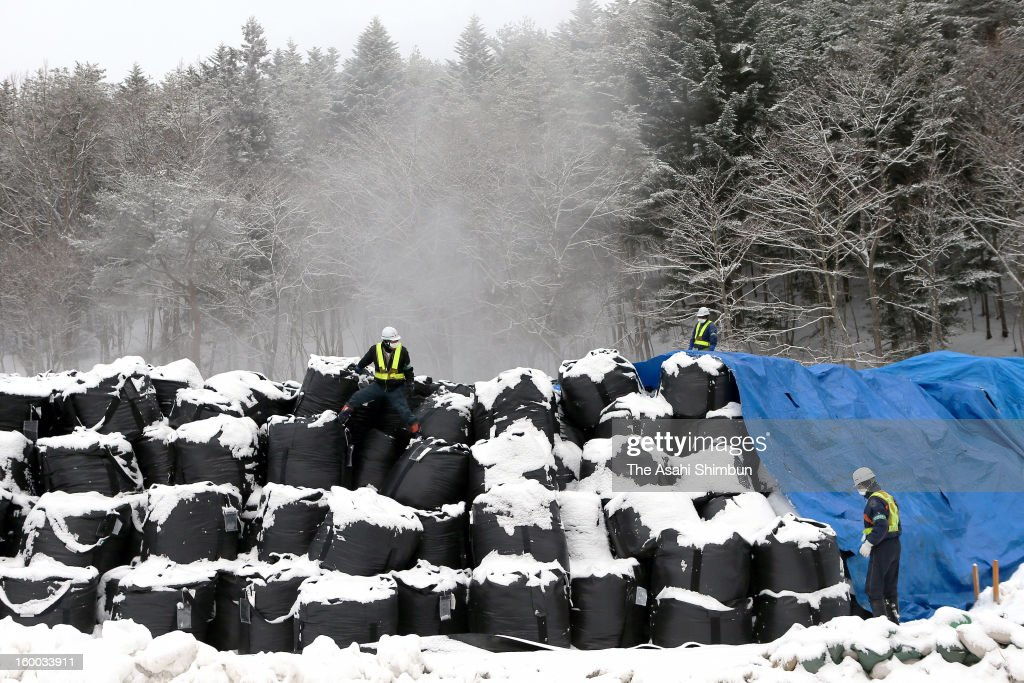 Steam rises from the snow covered bags containing the waste of radiation decontamination works such as vegetation and soil at a temporary yard on January 24, 2013 in Tamura, Fukushima, Japan. Recent snowfall in the most area of Tamura City, Iitate Village and Kawauchi village have suspended the decontamination work underway by Japanese government, the prospect of the restart will be March at the earliest, when the snow begin to melt.