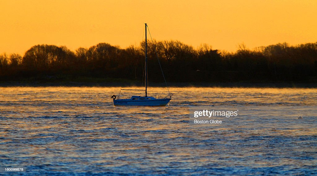 Steam rises off the water, which is warmer than the air, as the sun rises over a lone sailboat in South Boston, where temperatures this morning were 2 degrees in the morning with a -17 degrees wind chill factor.
