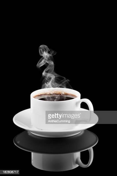 Steam rising from hot coffee in white cup and saucer