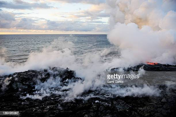 Steam rising off lava flowing into ocean