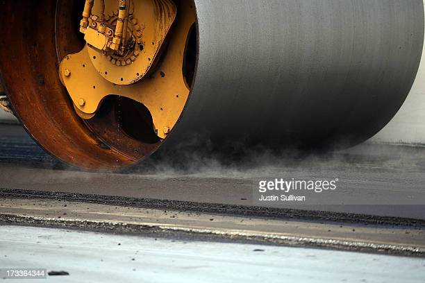 A steam roller flattens asphalt on the deck of the eastern span of the newly constructed San FranciscoOakland Bay Bridge on July 12 2013 in Oakland...