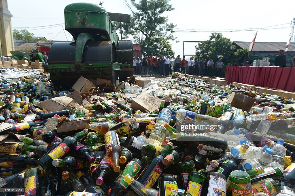 A steam roller machine destroys hundreds of alcohol drinks, pornographic and pirated video DVDs in a Jakarta police station on July 8, 2013, seized during recent raids in some areas of the Indonesian capital, as authorities prepare for Ramadan. Islam's holy month of Ramadan is celebrated by Muslims worldwide marked by fasting, abstaining from foods, sex and smoking from dawn to dusk for soul cleansing and strengthening the spiritual bond between them and the Almighty. AFP PHOTO / ADEK BERRY