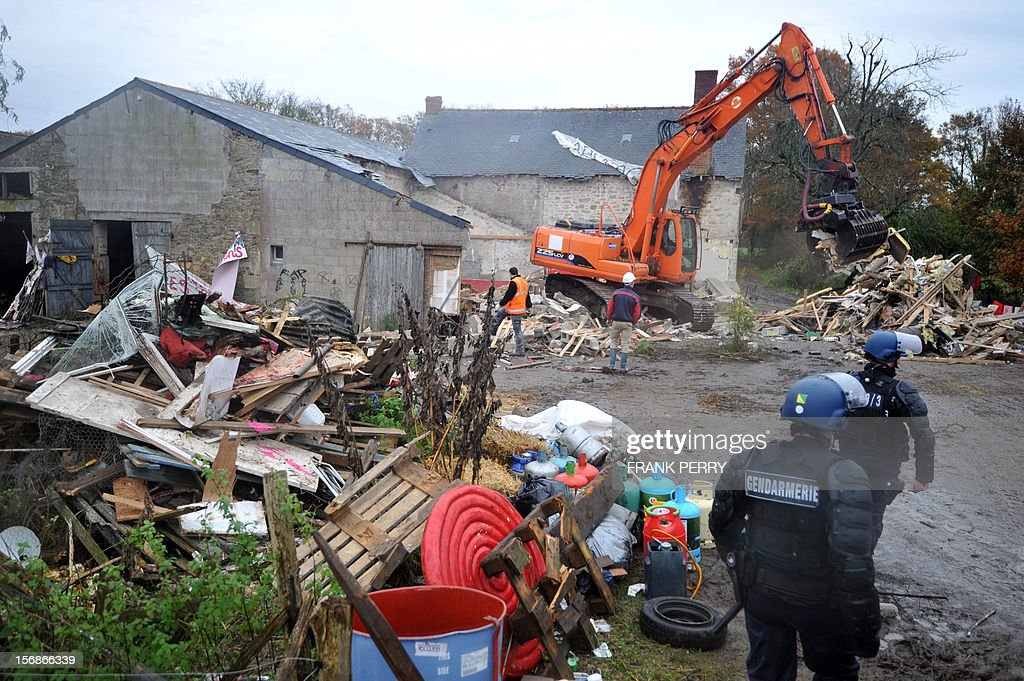A steam shovel destroys the farm squatted by protestors against a project to build an international airport, following its evacuation, on November 23, 2012 in Notre-Dame-des-Landes, western France. The battle led by opponents against the airport is also judicial, with multiple legal recourses ongoing. The project was signed in 2010 and the international airport is supposed to open in 2017 near the city of Nantes.