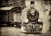 Steam train sorrounded by lots of smoke draws an passenger cabin, antique, sepia toned processed, wet plate and scratch processed,