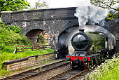 Steam train passing under a bridge