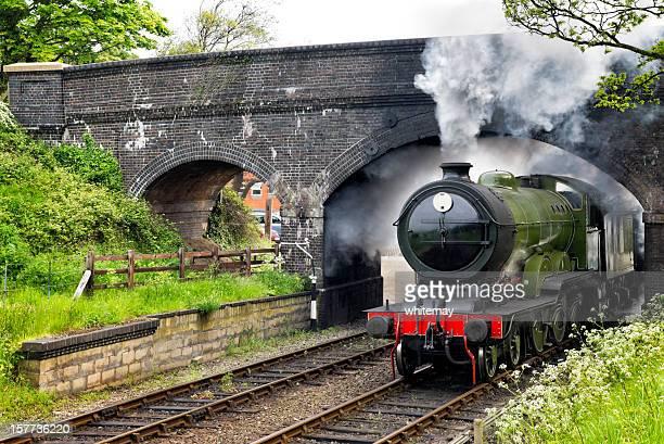 Treno a vapore passare sotto un ponte,