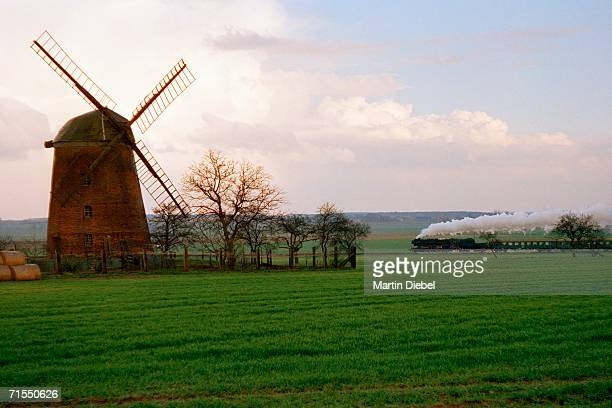 Steam train traveling past windmill in field