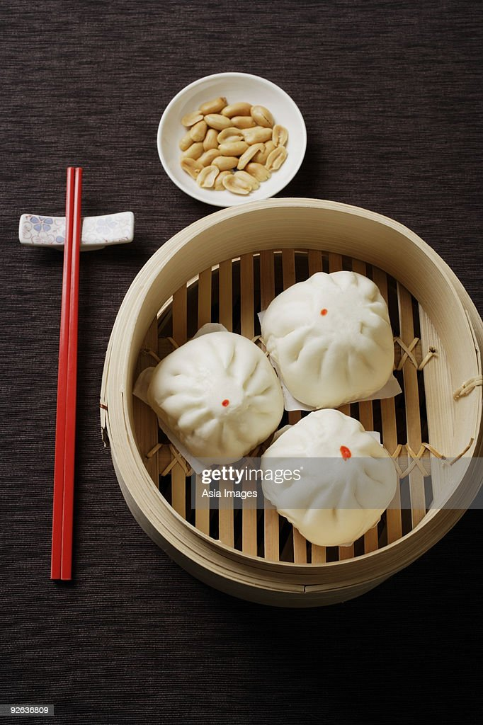 Steamed buns in bamboo steamers with red chopsticks