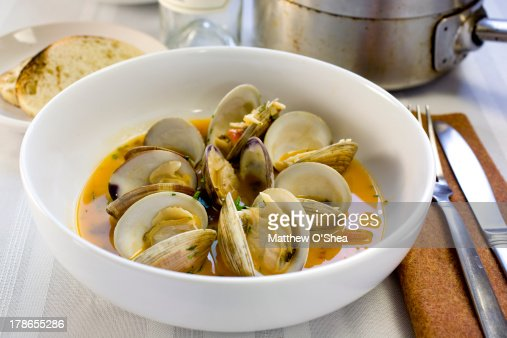 Steamed clams in tomato-garlic broth : Stock Photo