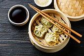 Steamed dumplings Dim Sum in bamboo steamer on black burned wooden background