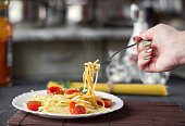 Steamed pasta spaghetti on a fork in tomato sauce with cheese and parsley, female hand. Italian spaghetti pasta on a dark stone background.