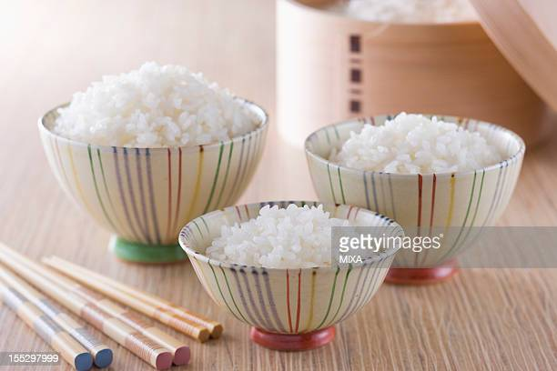 Steamed Rice in Three Sizes of Rice Bowls and Wooden Tub