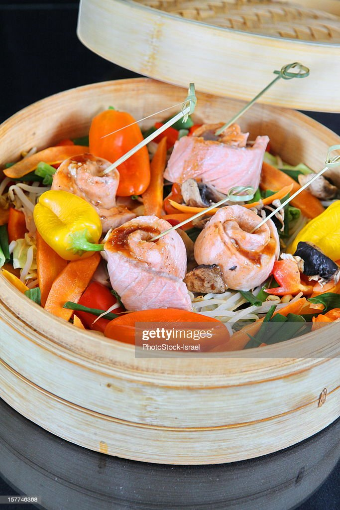 Steamed salmon with vegetables in a bamboo steamer : Stock Photo