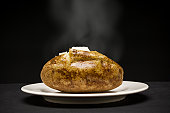 Steaming baked potato with butter