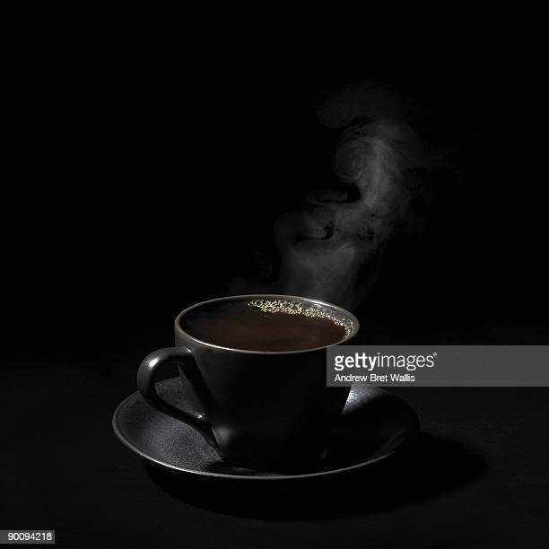 A steaming cup of black coffee against black