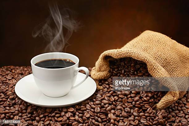 Steaming cup of coffee on pile of coffee beans