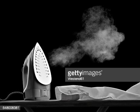 Steaming flat iron and shirt sleeve in front of black background