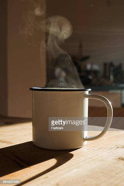 A steaming hot drink in a mug with sunlight, close-up