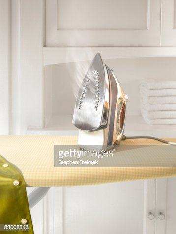 A steaming hot iron on a ironing board  : Stock Photo