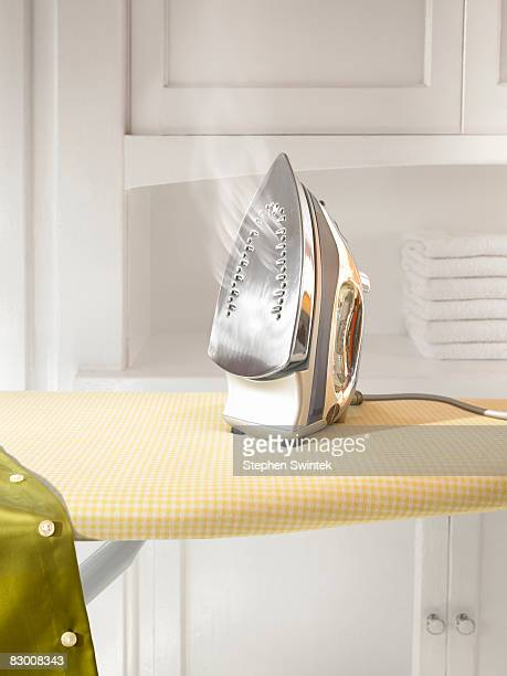A steaming hot iron on a ironing board