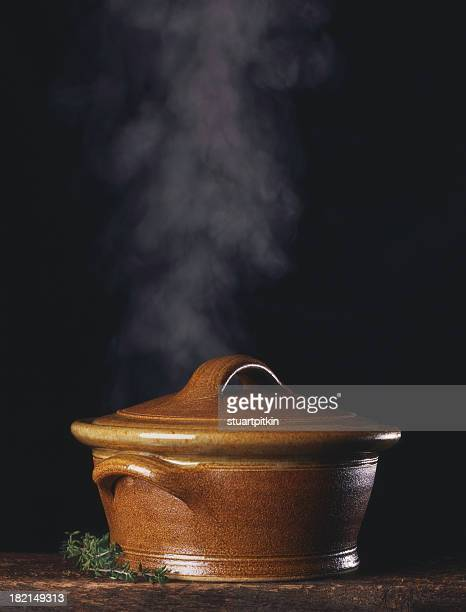 Steaming stock pot isolated on black on rustic wood table