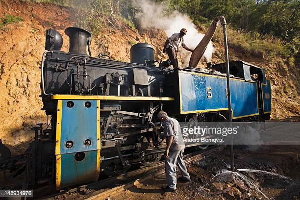 Steam-powered miniature train getting water refill and greasing between Mettupalayam and Udhagamandalam (Ooty) .