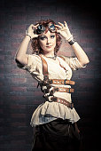 Beautiful redhair girl with steampunk Goggles standing on a brick wall background