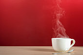 Steam rising from a large white porcelain cup of hot coffee or tea sitting with a silver spoon on a blonde colored wooden table against a red wall
