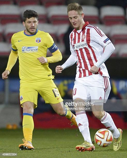 Steaua Bucharest's midfielder Cristian Tanase and AaB's midfielder Andreas Bruhn vie for the ball during the UEFA Europa League Group J football...