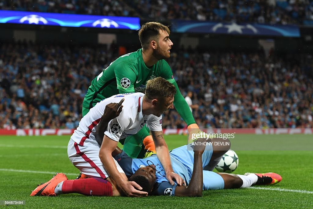 Steaua Bucharest's Romanian defender Bogdan Mitrea (C) checks on Manchester City's Nigerian striker Kelechi Iheanacho (R) who got injured during the UEFA Champions league second leg play-off football match between Manchester City and Steaua Bucharest at the Etihad Stadium in Manchester, north west England on August 24, 2016. / AFP / Anthony Devlin