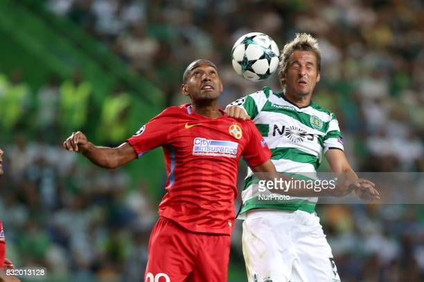 Steaua's midfielder William Amorim heads the ball with Sporting's defender Fabio Coentrao from Portugal during the UEFA Champions League playoffs...