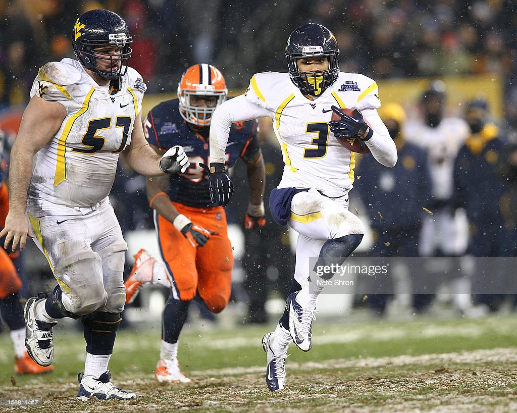 Stedman Bailey #3 of the West Virginia Mountaineers runs the ball with teamate Jeff Braun #57 as they are chased by Dyshawn Davis #35 of the Syracuse Orange during the New Era Pinstripe Bowl at Yankee Stadium on December 29, 2012 in the Bronx borough of New York City.