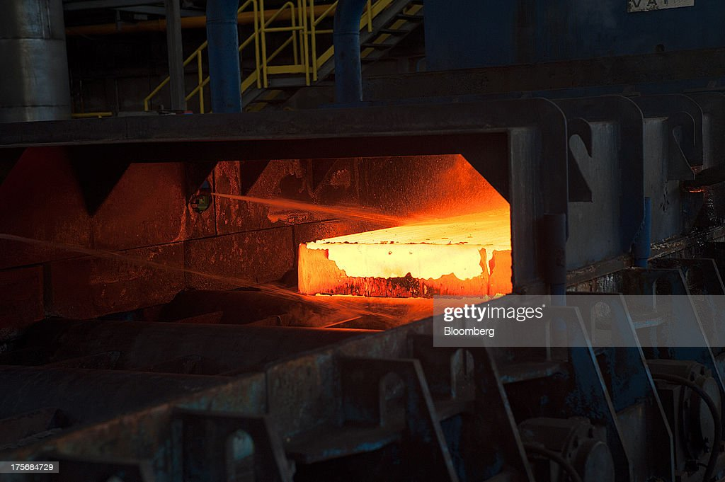 A steel bar is heated to 1000 degrees centigrade as it passes through the primary descaler in the hot strip shop at the ArcelorMittal Poland SA steel mill in Krakow, Poland, on Tuesday, Aug. 6, 2013. ArcelorMittal, the biggest steelmaker globally and in Poland, said on March 15 it expects European demand to slide before rebounding in 2014. Photographer: Will Boase/Bloomberg via Getty Images