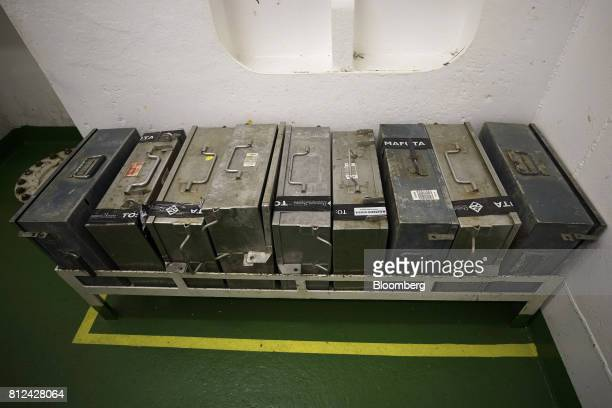 Steel cases used to transport sealed cans of offshore diamonds from ship to shore sit in a storage rack aboard the Mafuta diamond mining vessel...